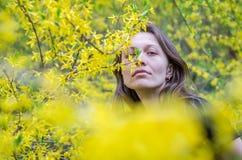 Den unga härliga flickan bland gulingen blommar på buskarna på ljus solig dag Arkivbilder