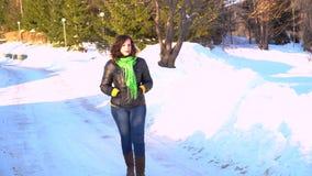 Den unga härliga flickan går på snön utomhus stock video