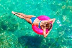 Den unga härliga flickan i bikini simmar i ett tropiskt hav på en rubb fotografering för bildbyråer