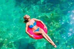 Den unga härliga flickan i bikini simmar i ett tropiskt hav på en rubb royaltyfri foto