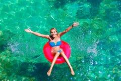 Den unga härliga flickan i bikini simmar i ett tropiskt hav på en rubb arkivbild