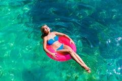 Den unga härliga flickan i bikini simmar i ett tropiskt hav på en rubb royaltyfria bilder