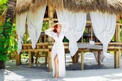 Den unga härliga flickan i den vita klänningen står därefter en bambu som förlägga i barack på royaltyfri foto