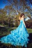 Den unga härliga flickan i en frodig blått klär Arkivbilder