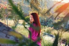 Den unga härliga flickan i en ljus rosa färg klär med en bukett av ye Royaltyfria Bilder