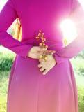 Den unga härliga flickan i en ljus rosa färg klär med en bukett av ye Royaltyfri Bild