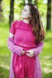 Den unga härliga flickan i ett rosa lag och en rosa kort klänning startar r Arkivbilder