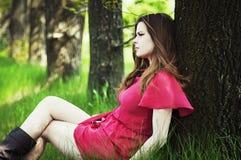 Den unga härliga flickan i ett rosa lag och en rosa kort klänning startar r Arkivfoto