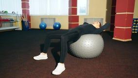 Den unga härliga flickan i idrottshallen, svänger pressen med bollen för kondition som förbättrar musklerna av pressen och baksid lager videofilmer