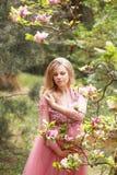 Den unga härliga flickan i lång klänning trycker på hennes gravida buk nära blommande magnolia parkerar in Arkivfoto