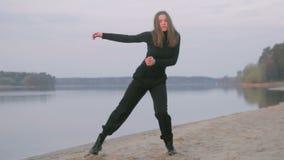 Den unga härliga flickan i svart beklär dans, på flodstranden, konturn stock video