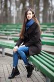 Den unga härliga flickan i svarta exponeringsglas för en lagblåtthalsduk som sitter på bänk i stad, parkerar En elegant brunettfl Royaltyfria Bilder