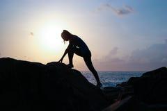 Den unga härliga flickan idrottskvinnan, i sportsweargymnastikskor hoppar vaggar igenom på solnedgången, en höjdhopp, gymnastik,  arkivbild