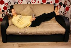 Den unga härliga flickan ligger på soffan och lyssnar till musik på hörlurar med mobiltelefonen Royaltyfri Fotografi
