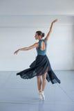 Den unga härliga flickan med brunbränd hud dansar i studion Ballerinasnurr i dansen arkivfoto