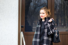 Den unga härliga flickan med den trendiga påsen står på set Royaltyfri Fotografi