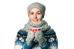 Den unga härliga flickan med en kopp i händer övervintrar ståenden på vit bakgrund, copyspace Royaltyfri Bild