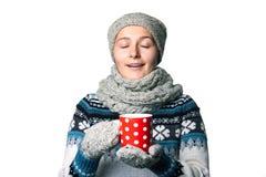 Den unga härliga flickan med en kopp i händer övervintrar ståenden på vit bakgrund, copyspace Royaltyfri Fotografi