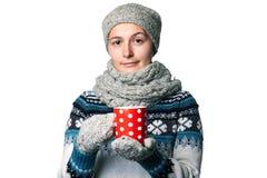 Den unga härliga flickan med en kopp i händer övervintrar ståenden på vit bakgrund, copyspace Royaltyfria Foton