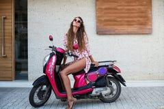 Den unga härliga flickan med långt hår i solglasögon i det rosa skjorta- och bruntskodonet som poserar på sparkcykeln, framkallar royaltyfri bild