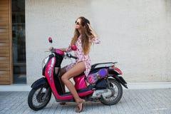 Den unga härliga flickan med långt hår i solglasögon i det rosa skjorta- och bruntskodonet som poserar på sparkcykeln, framkallar Fotografering för Bildbyråer