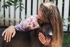 Den unga härliga flickan med långt hår spelar med hundkapplöpning royaltyfri foto