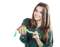 Den unga härliga flickan med mörkt hår isolerade på en vit bakgrund som rymmer ett äpple med en måttband leende Royaltyfri Fotografi