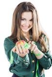 Den unga härliga flickan med mörkt hår isolerade på en vit bakgrund som rymmer ett äpple med en måttband leende Royaltyfria Foton