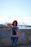Den unga härliga flickan med rött hår poserar mot bakgrunden av floden och järnvägsbron Arkivbild