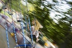 Den unga härliga flickan rider på en gunga inställd på kedjor Royaltyfri Bild