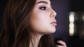 Den unga härliga flickan ser i spegeln och rätar ut hennes ganska hår i den yrkesmässiga makeupstudion, flicka får stock video