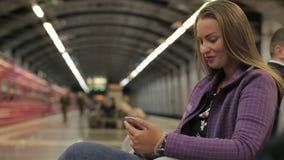 Den unga härliga flickan skriver meddelandebruk en smartphone lager videofilmer
