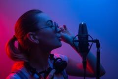 Den unga härliga flickan skriver vocals, showbusiness, discjockeyn, sammankomsten, popmusik I färgljus blått-rött och rök royaltyfria foton