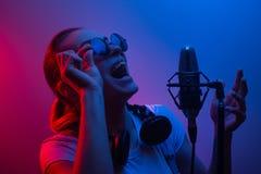 Den unga härliga flickan skriver vocals, showbusiness, discjockeyn, sammankomsten, popmusik I färgljus blått-rött och rök royaltyfri fotografi