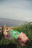 Den unga härliga flickan som ligger med hennes ögon, stängde sig och ett leende på hans framsida det gröna gräset den varma solig Arkivfoton