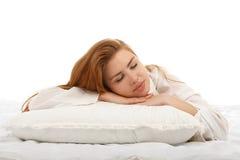 Den unga härliga flickan sover i sängen som kramar en kudde på hans s Royaltyfri Foto