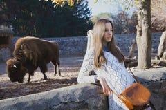 Den unga härliga flickan står nära aviariet med bisonen i stad z Royaltyfri Bild