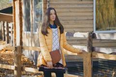 Den unga härliga flickan står nära trästaketet i stadszoo Arkivfoto