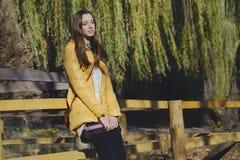 Den unga härliga flickan står nära trästaketet i stadszoo Arkivfoton