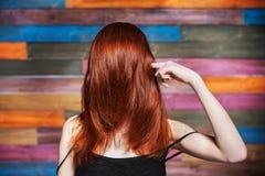 Den unga härliga flickan täckte framsidan vid långt rött hår Arkivfoton