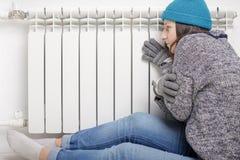 Den unga härliga flickan värme händer nära ett element arkivbild