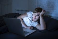 Den unga härliga internet missbrukade den sömnlösa och trötta kvinnan som sent arbetar på bärbara datorn i säng på natten royaltyfri fotografi