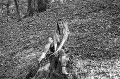 Den unga härliga kvinnamodellen med långt hår i jeans och en ärmlös tröja går till och med Forestet Park bland träd och att poser Arkivbild
