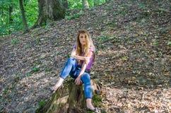 Den unga härliga kvinnamodellen med långt hår i jeans och en ärmlös tröja går till och med Forestet Park bland träd och att poser Arkivfoton