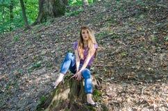 Den unga härliga kvinnamodellen med långt hår i jeans och en ärmlös tröja går till och med Forestet Park bland träd och att poser Royaltyfri Fotografi