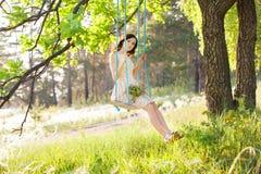 Den unga härliga kvinnan är svängande på en gunga i sommarskog fotografering för bildbyråer