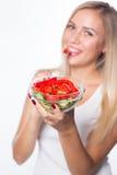 Den unga härliga kvinnan äter grönsaksallad äta som är sunt Att att vara i form Arkivbilder