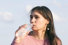 Den unga härliga kvinnan dricker vatten royaltyfri foto