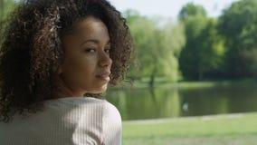 Den unga härliga kvinnan för det blandade loppet med lockigt afro hår som lyckligt ler i en gräsplan, parkerar stock video