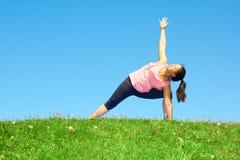 Den unga härliga kvinnan för det blandade loppet som gör yogakrigaren, poserar arkivbild